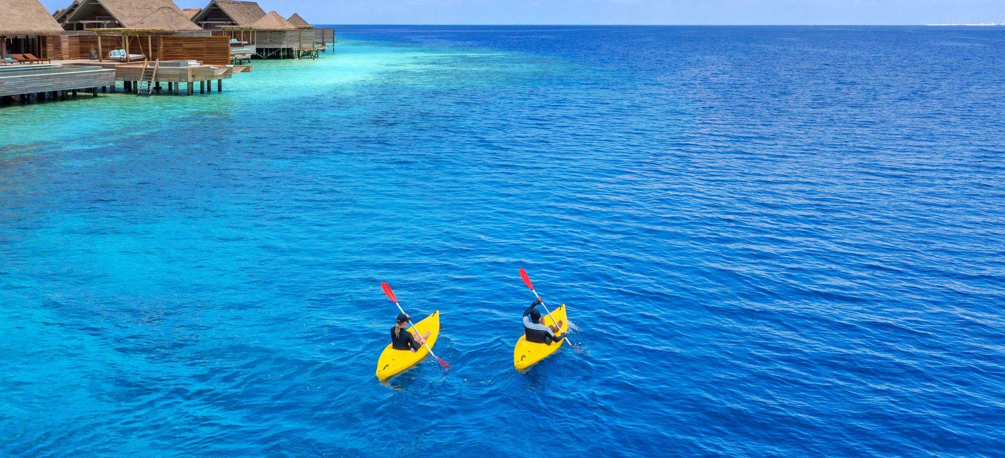 Paar in einzelnen Kajaks rudert vorbei an den Wasservillen des Waldorf Astoria Maldives, mit Blick auf das offene Meer
