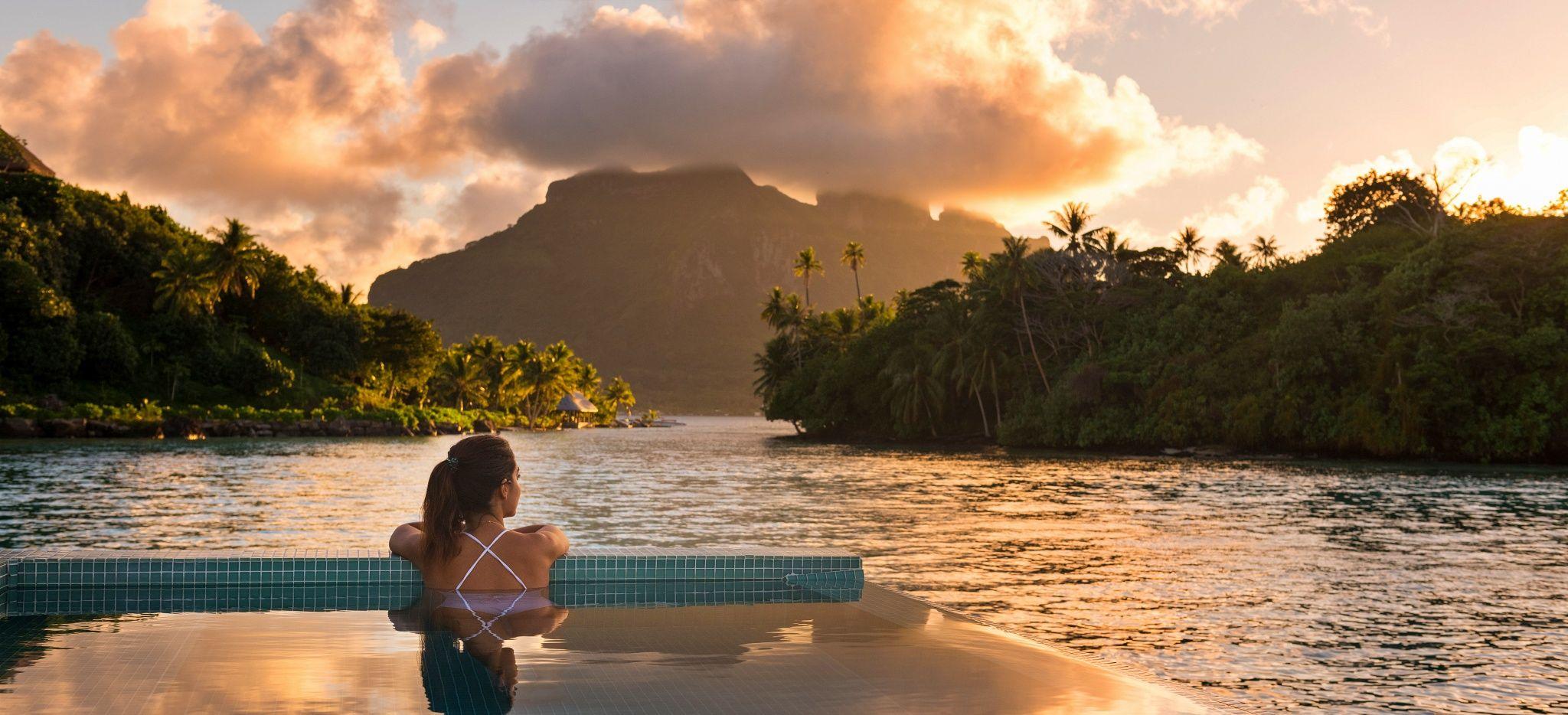 "Eine Frau blickt aus dem Pool der Royal Villa im Hotel ""Conrad Bora Bora Nui"" auf die Insel Bora Bora"