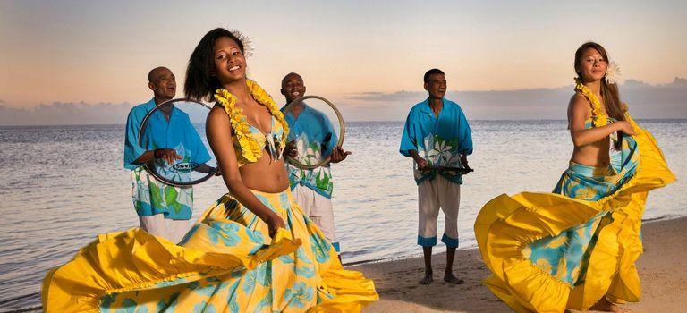 Sega Tänzerinnen vor drei Musikern an einem Strand auf Mauritius
