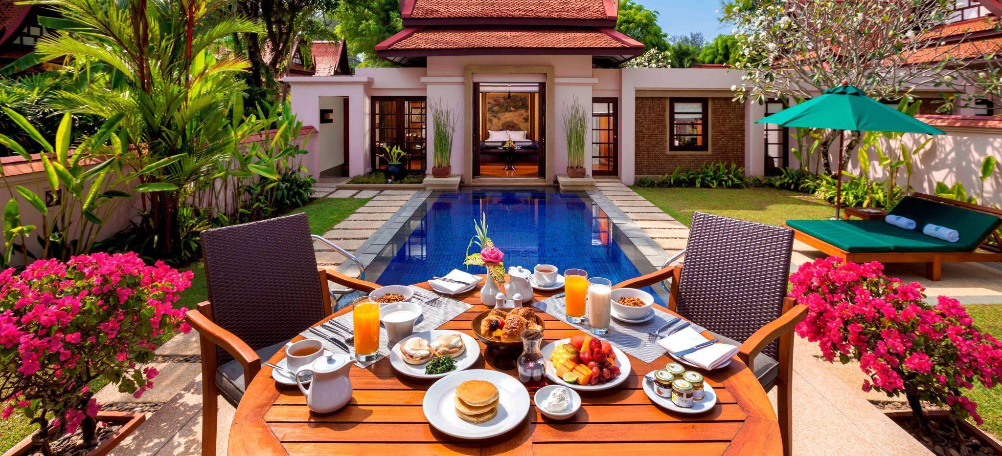 """Ein Frühstück steht auf einem Tisch vor einem Pool im Innenhof der """"Signutaure Pool Villa"""" des Banyan Tree Phuket"""