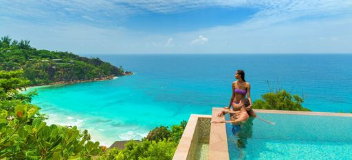 Paar badet in einem Infinity Pool mit Blick auf den Strand Petite Anse im Hotel Four Seasons Resort Seychelles