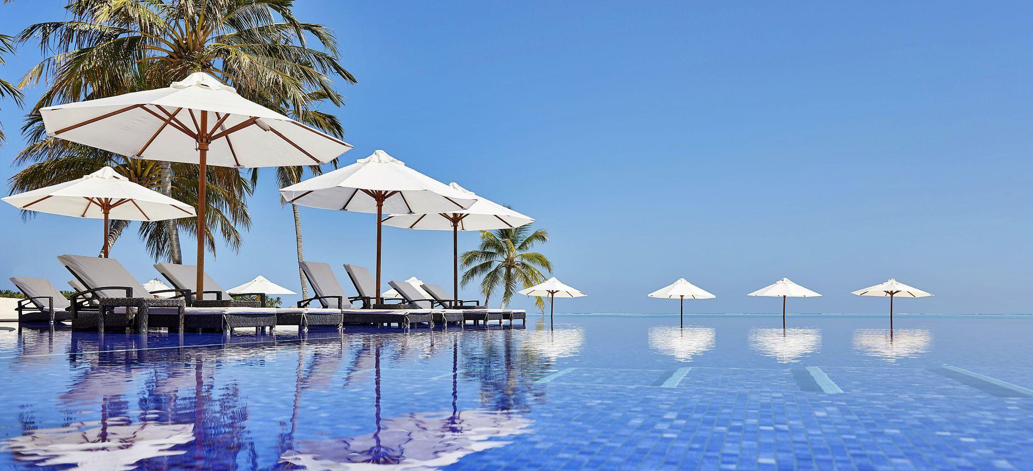 Ein Langer Pool mit Strandliegen und Sonnenschirmen im Hotel Conrad Maldives