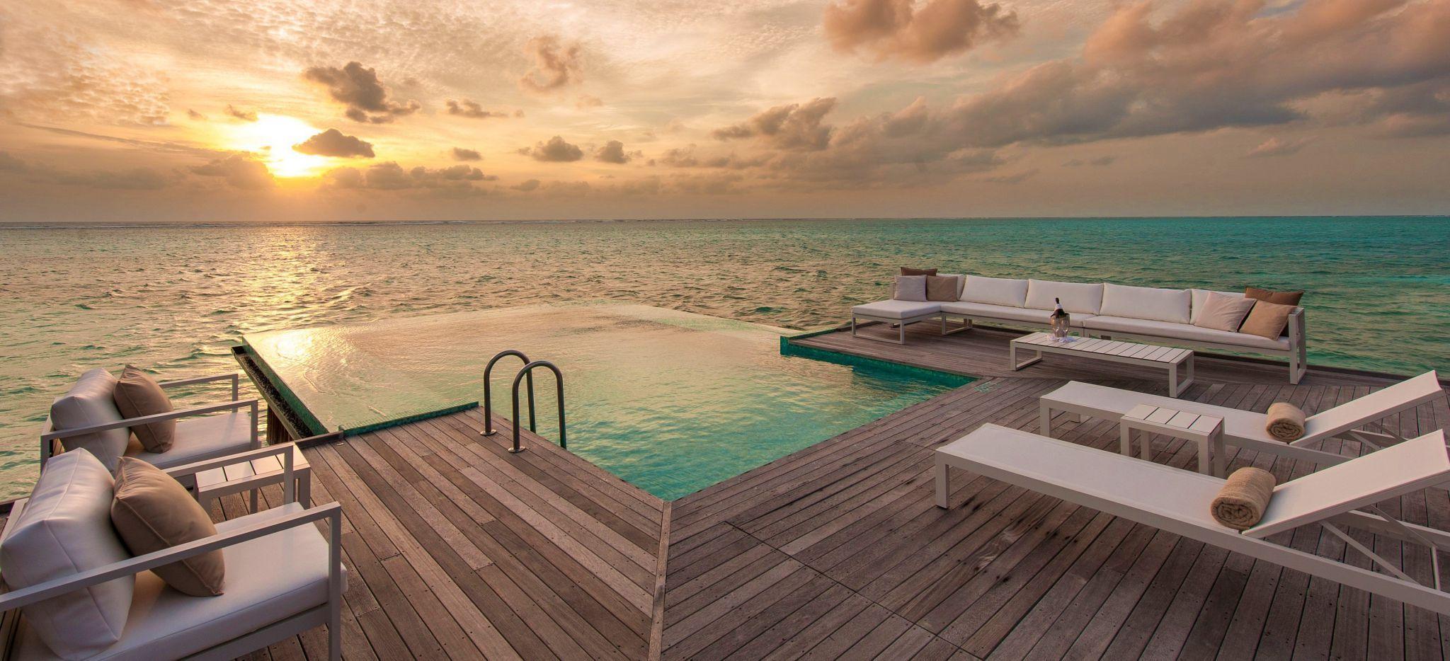 Eine Terrasse über Wasser mit privatem Pool und Blick auf den Sonnenuntergang über dem Meer der Malediven