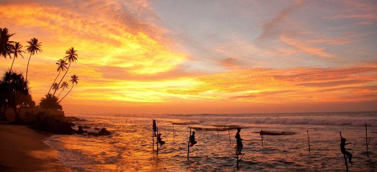 Manner fischen auf Stelzen im Wasser an einem Strand auf Sri Lanka, im Abendrot