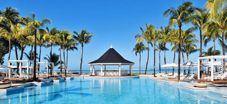 Ein großer Pool in einer Palmenallee in Richtung Meer, ein Pavillon dazwischen