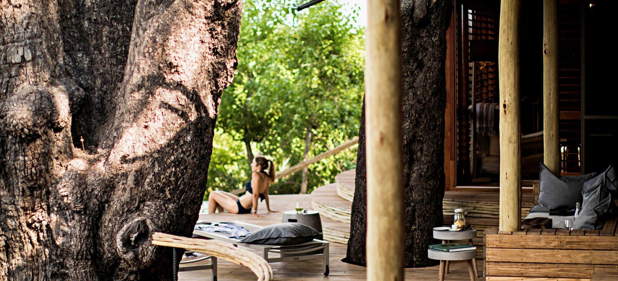"""Eine Frau sonnt sich auf der Terrasse eines der Hotelzimmer der Safari-Lodge """"Little Mombo"""" in Botsuana"""