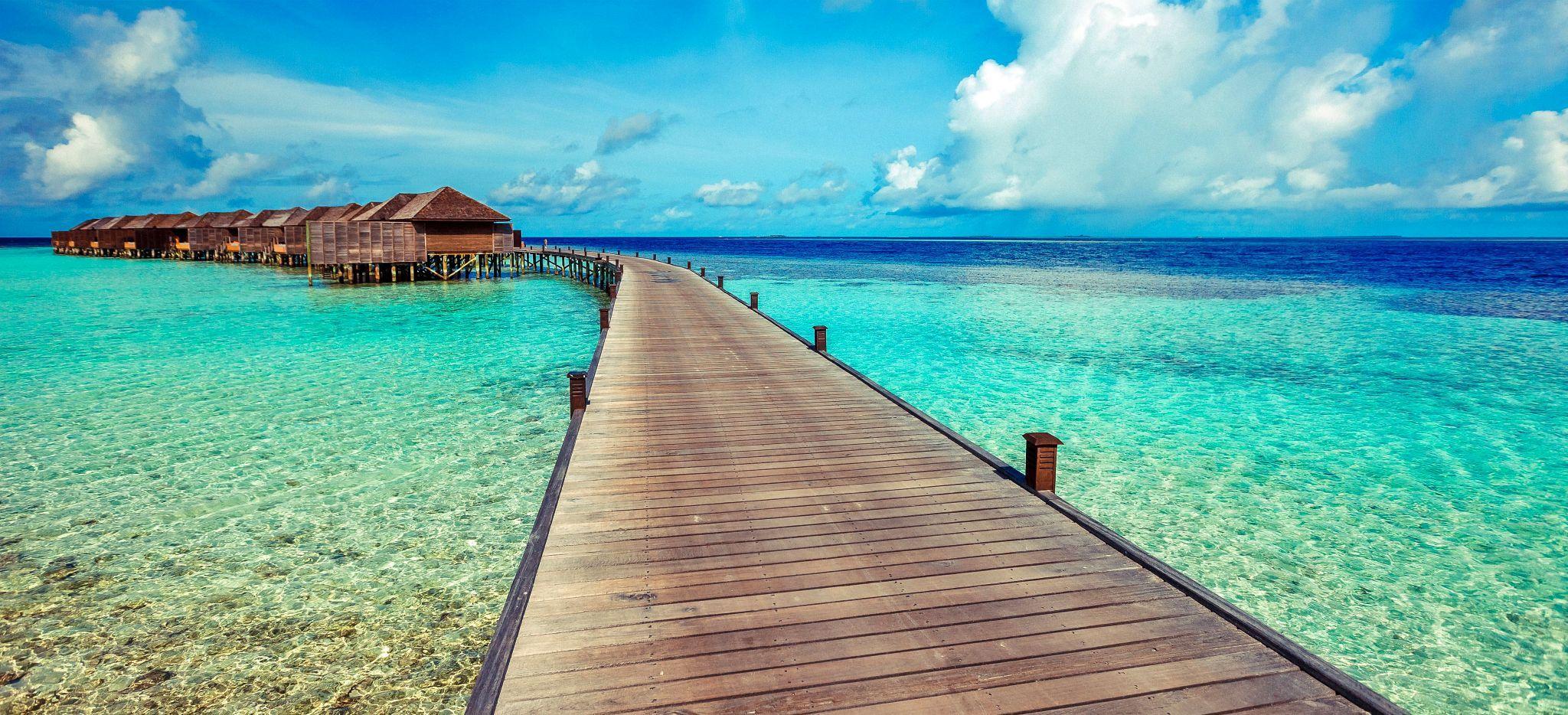 Ein langer Steg in der Lagune der Malediveninsel Lily Beach mit den Wasservillen des Hotels
