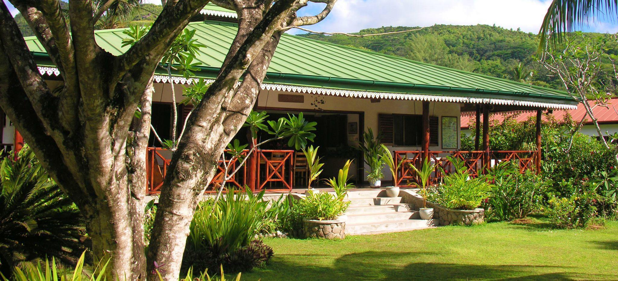 Ein großes Kolonialhaus mit grünem Dach durch einen tropischen Garten gesehen. Aufgenommen in der Villa Bambou auf den Seychellen