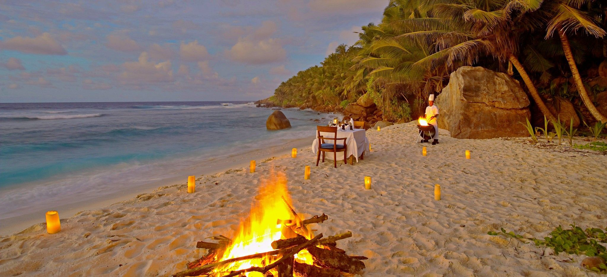 Ein Lagerfeuer am Strand, neben einem gedeckten Tisch, auf Frégate Island, Seychellen
