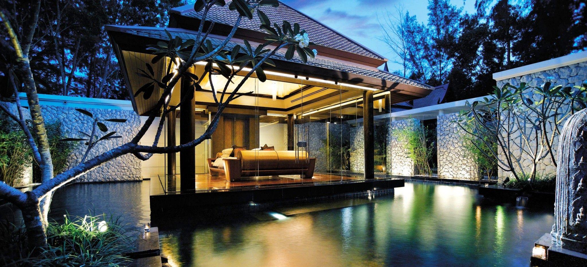 Ein Pavillion in der Mitte einer Pools bei Nacht, beleuchtet
