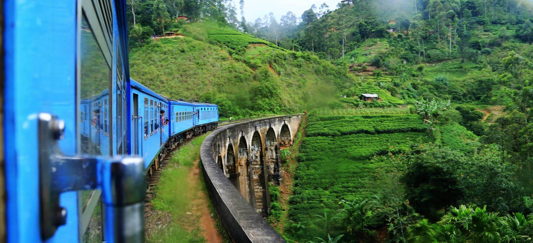 Ein blauer Zug fährt im Regen um die Kurve über eine Brücke in den Bergen von Sri Lanka