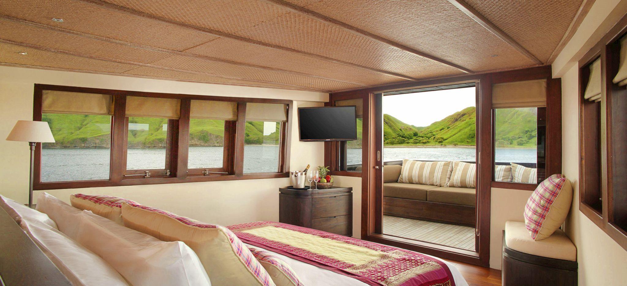 """Hotelzimmer des Schiffes """"Alila Purnama"""", Master Suite mit Balkon mit Blick auf das Meer, Inseln in der Ferne, Indonesien"""