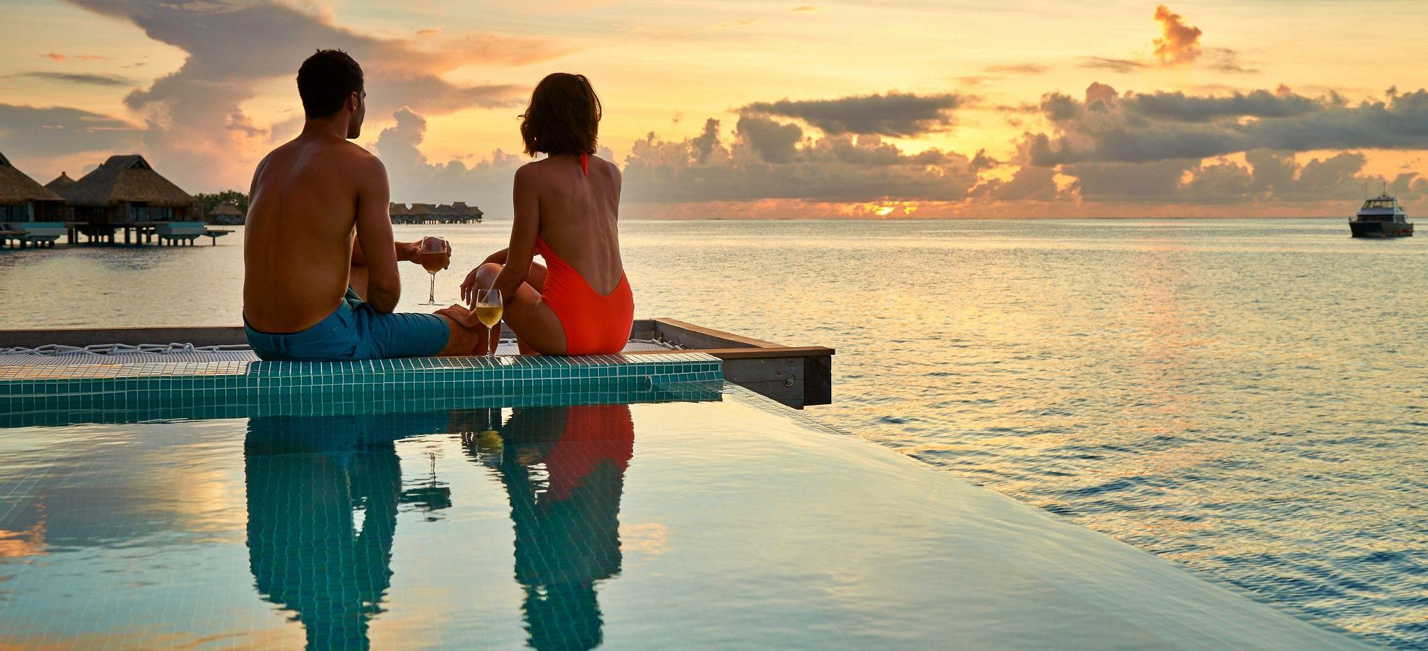 Ein Paar sitzt an der Kante eines Pools und betrachtet den Sonnenuntergang