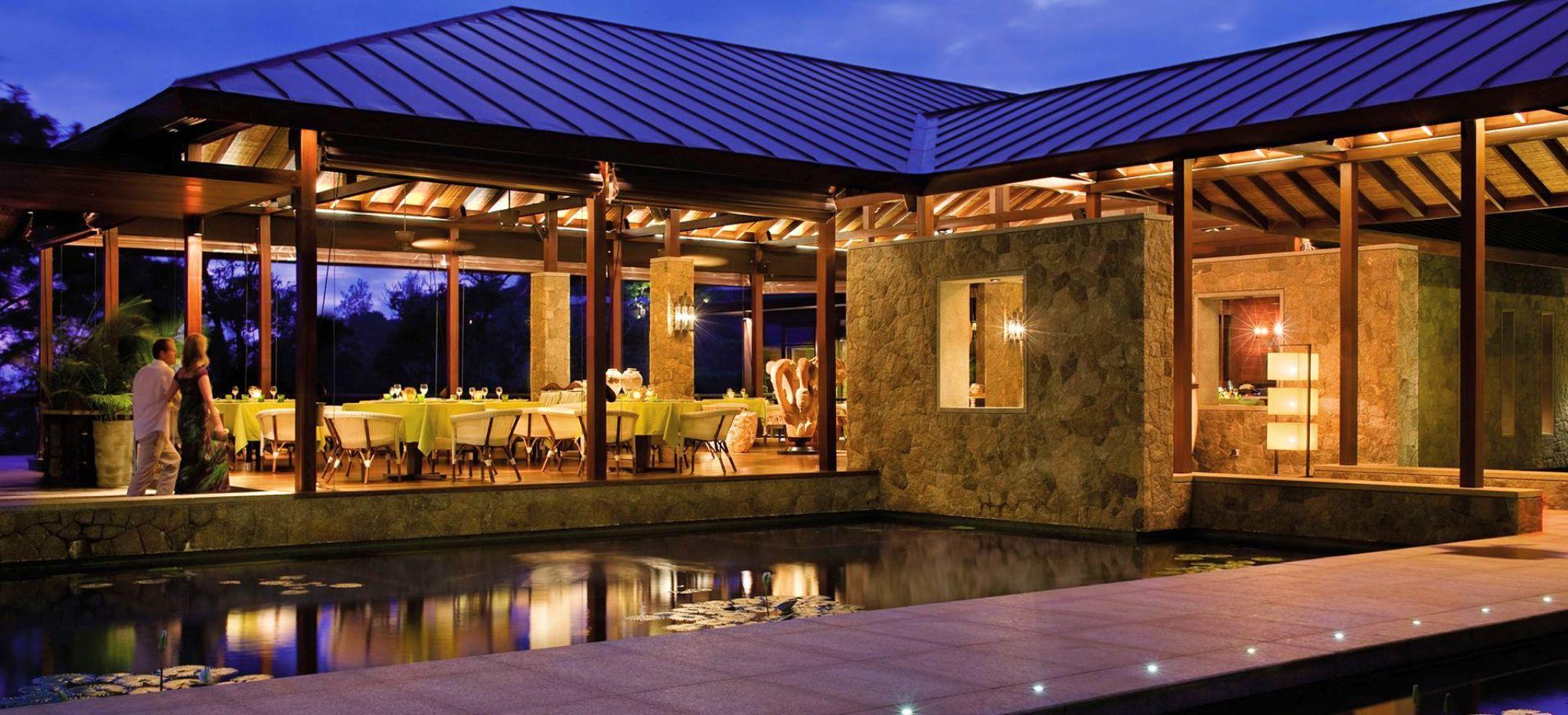 Ein Restaurant des Four Seasons Resort Seychelles bei Nacht. Das Restaurant ist umgeben von Wasser