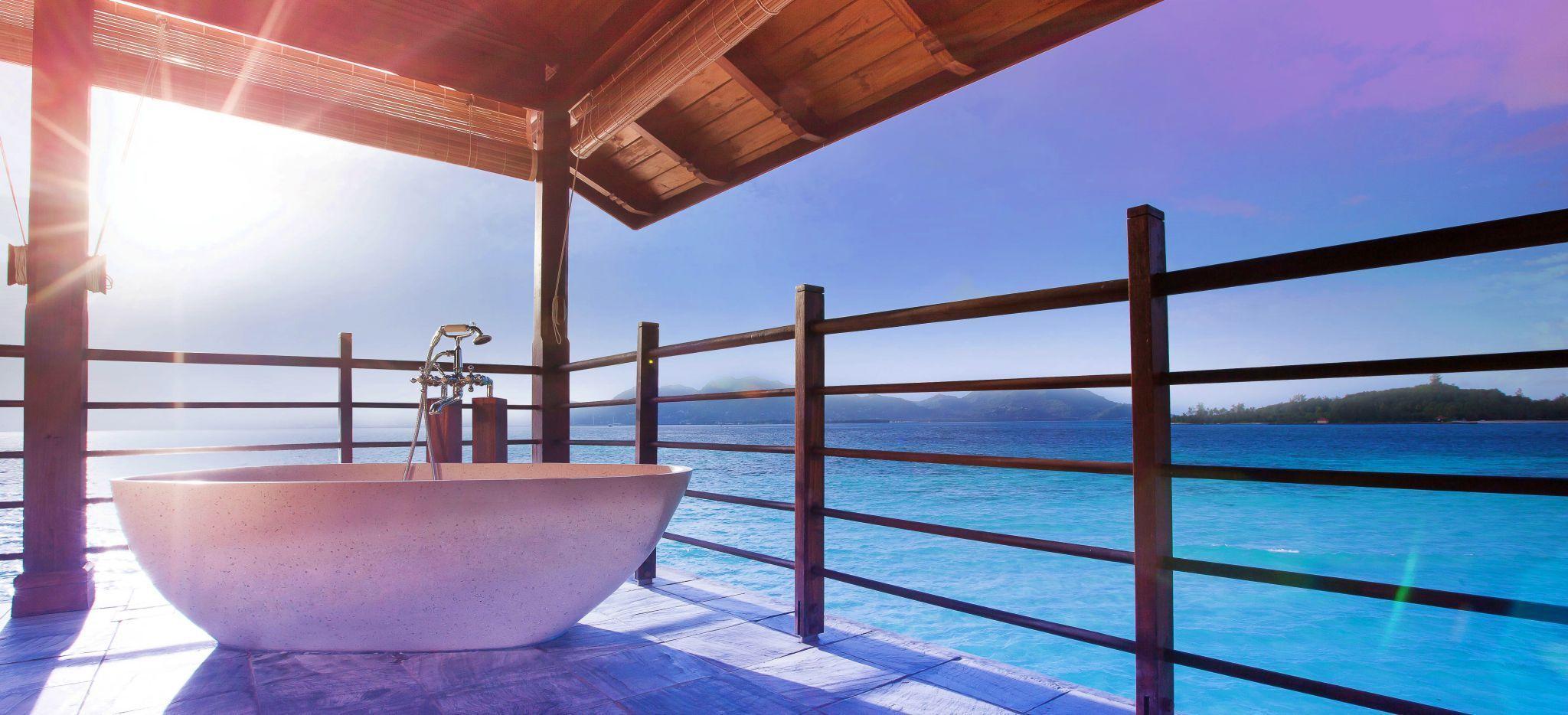 Badewanne auf einer Terrasse über dem Meer im Sonnenlicht, im Hotel JA Enchanted Island auf den Seychellen