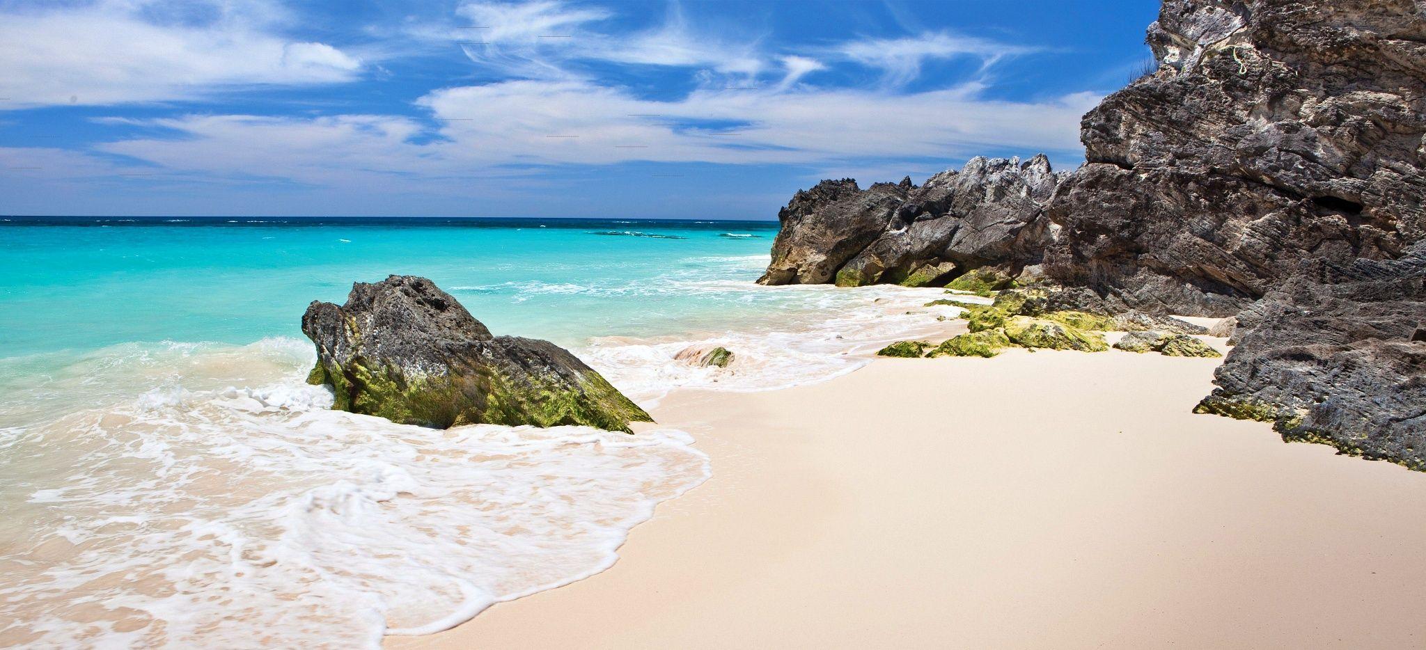 """Ein weißer Sandstrand mit großen Felsen vor dem Hotel """"Rosewood Tucker's Point"""" auf den Bermudas"""