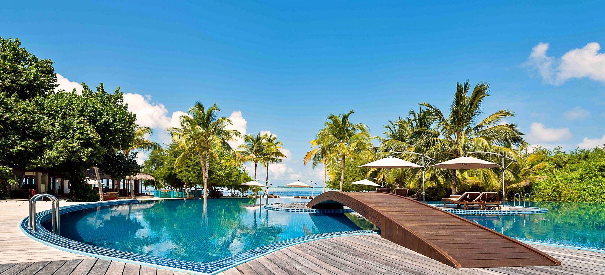 Ein Pool mit einer Holzbrücke, von Palmen umsäumt