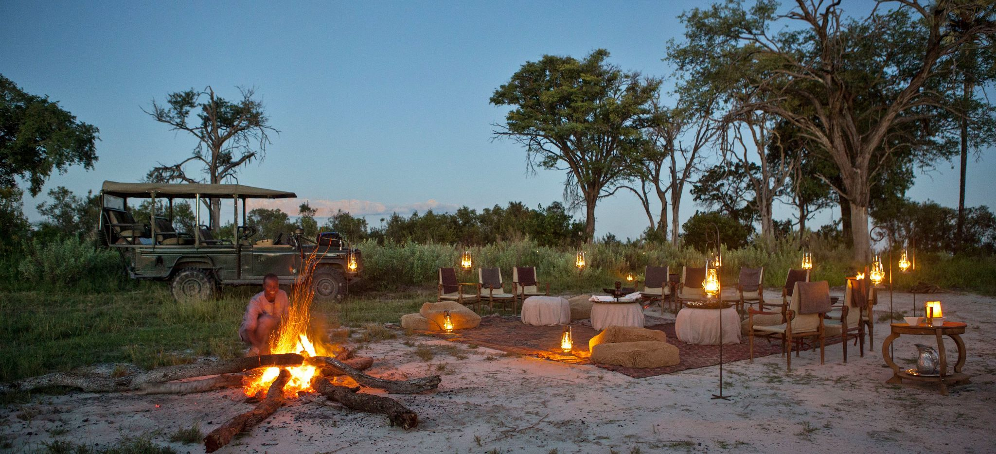 A guide is fanning a fire in the Okavango Delta, another is preparing a Dinner in the Wilderness.