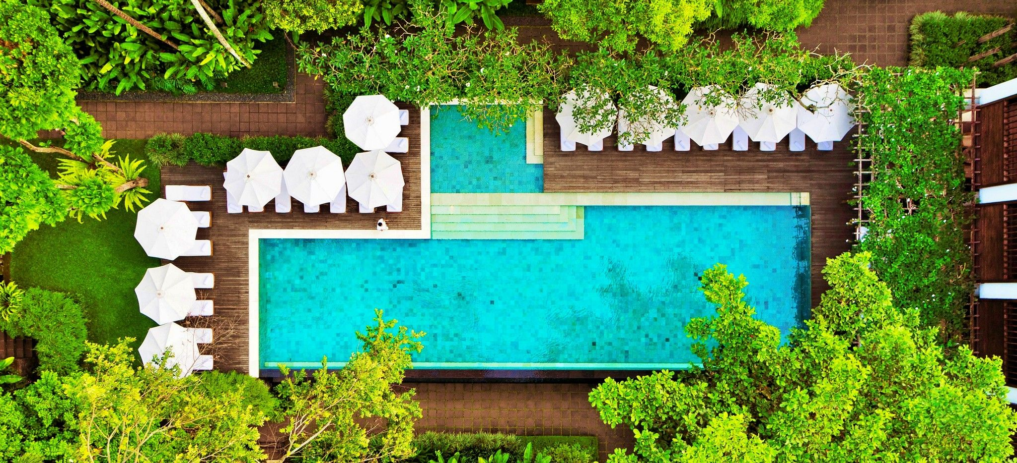 Ein Pool in einer Holzterrasse eingelassen, außern herum Sonnenschirme und Strandiegen und der balinesische Dschungel