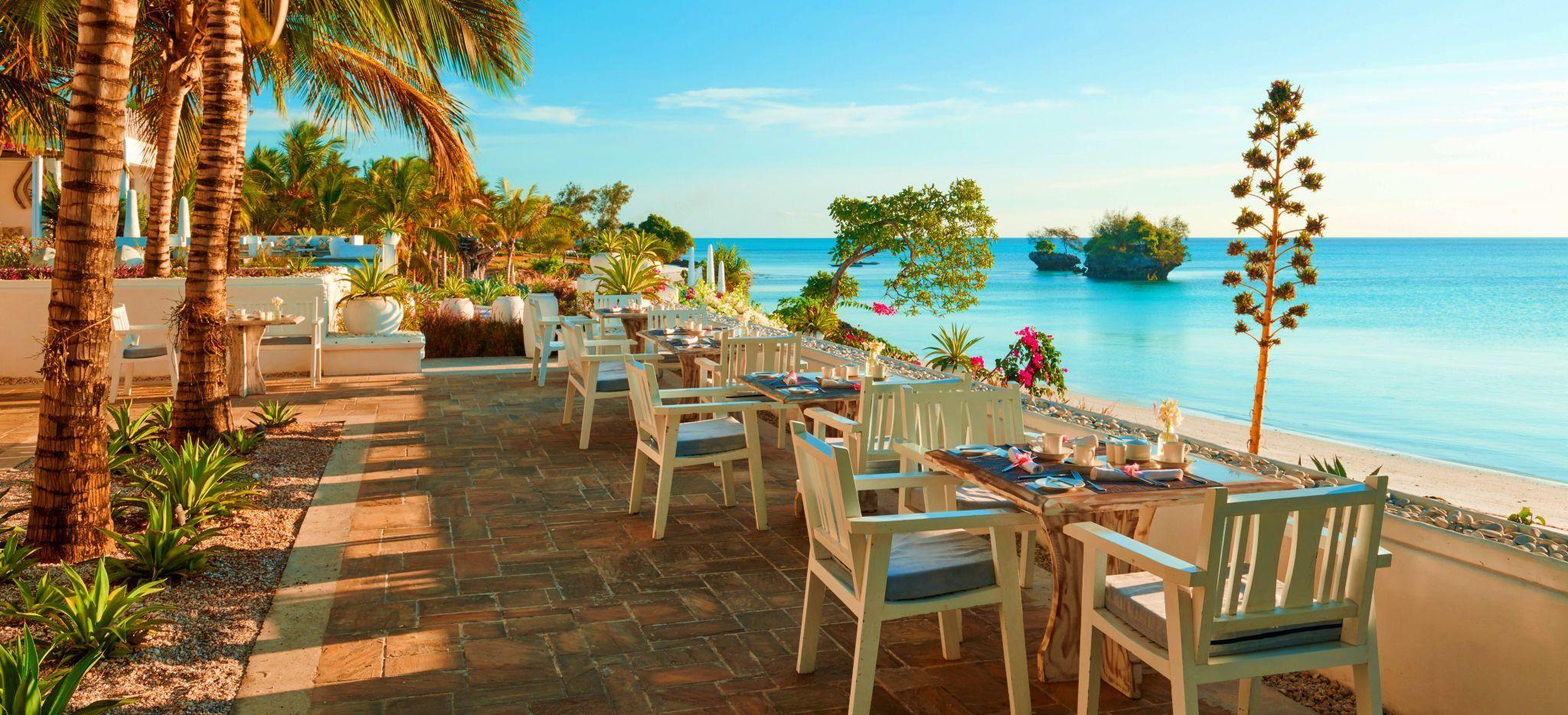 Ein paar Restauranttische mit Blick auf das Meer, im Hotel the Aiyana auf Pemba, Tansania