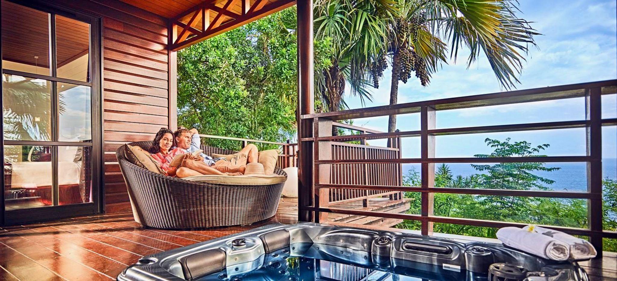 Ein Paar sitzt auf einer Terrasse mit Jacuzzi im Hotel Palm auf La Réunion