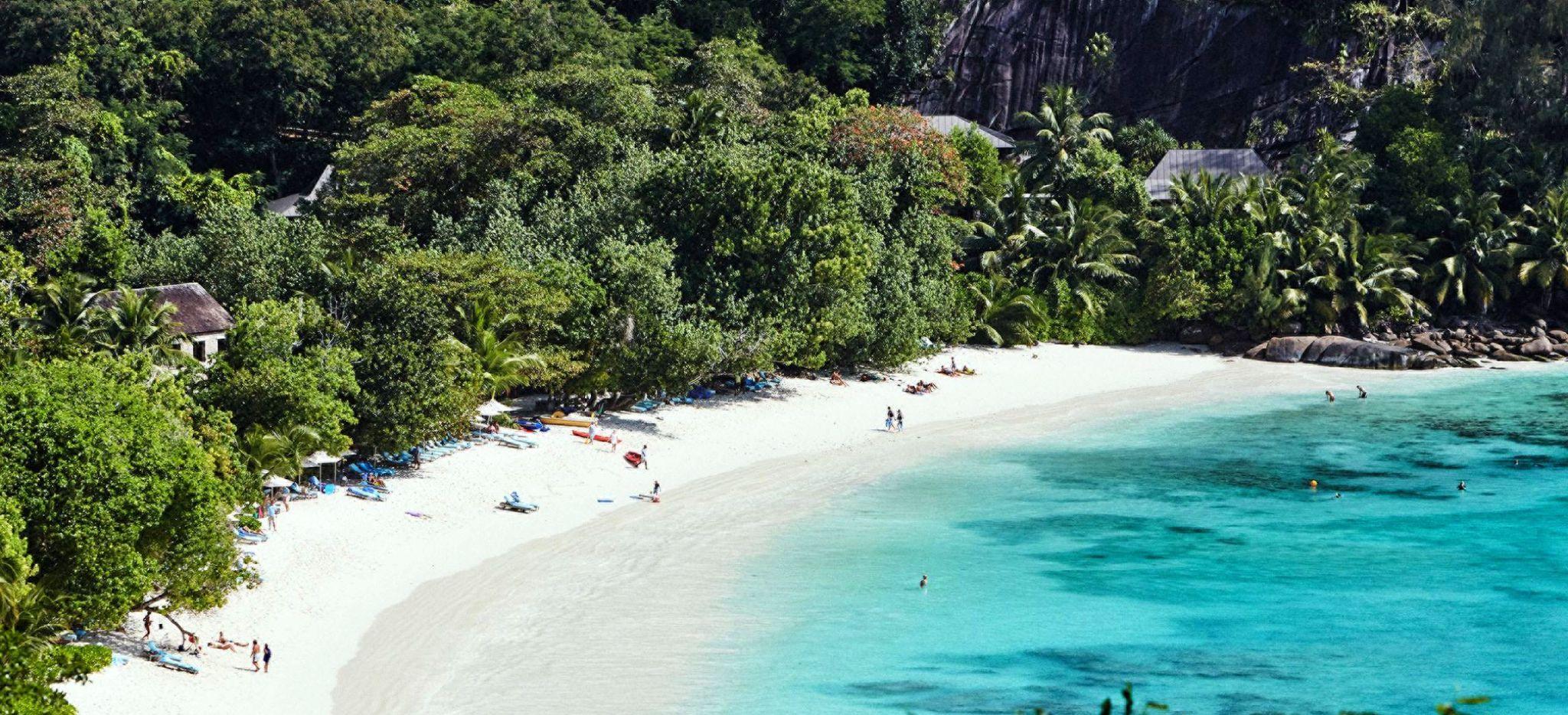 Der Strand Petite Anse mit dem Hotel Four Seasons Resort Seychelles und Gästen am Strand und im Meer.
