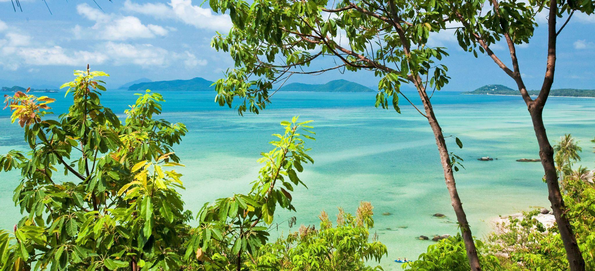 Blick auf das Meer und das Festland durch Bäume, aufgenommen im Hotel Kamalaya, Thailand