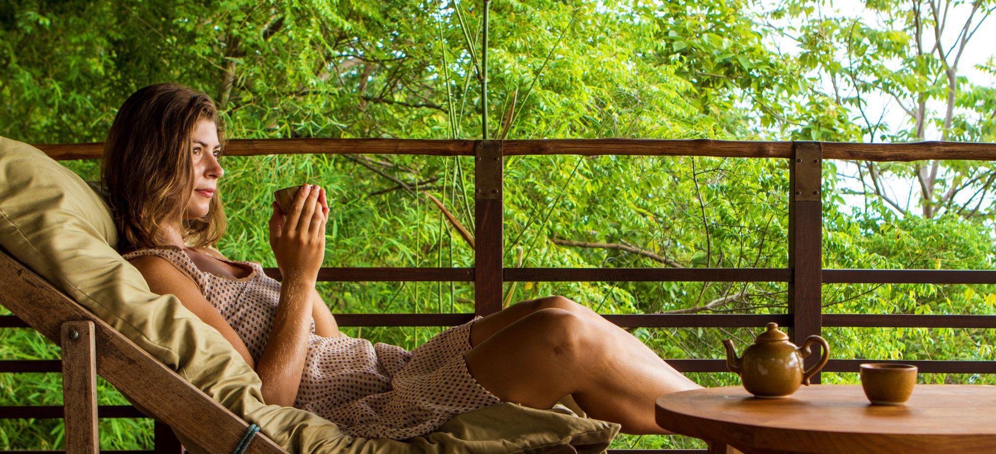 Frau entspannt mit Tee in einer Sonnenliege im Hotel Kamalaya in Thailand