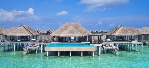 Eine Wasservilla mit privatem Pool über einer türkisen Lagune