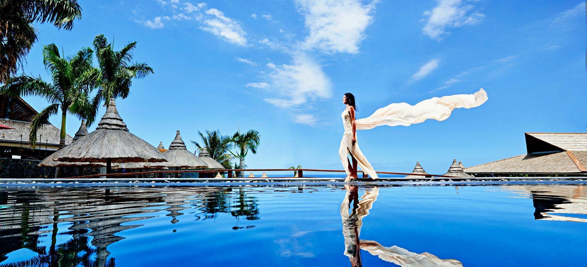 Eine Frau spaziert am Rand des Hauptpools des Hotels Palm auf La Réuion