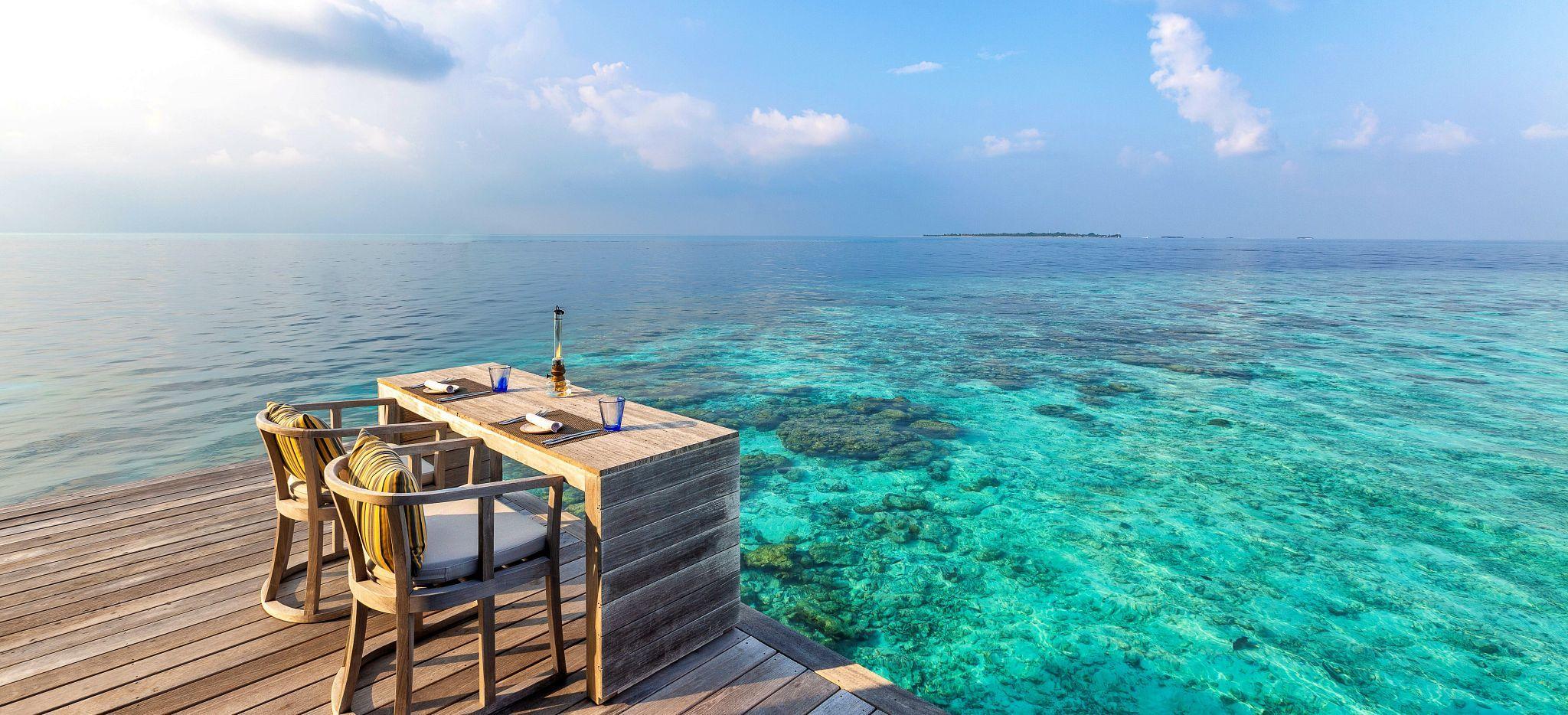 """Ein gedeckter Tisch auf einer Plattform direkt über der Lagune der Malediveninsel """"Hurawalhi"""""""