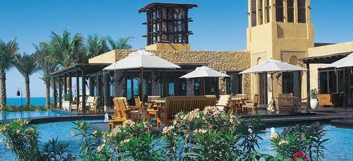 """Pool mit Hauptrestaurant im Hotel """"One&Only Royal Mirage"""", Palmen und Meer im Hintergrund"""