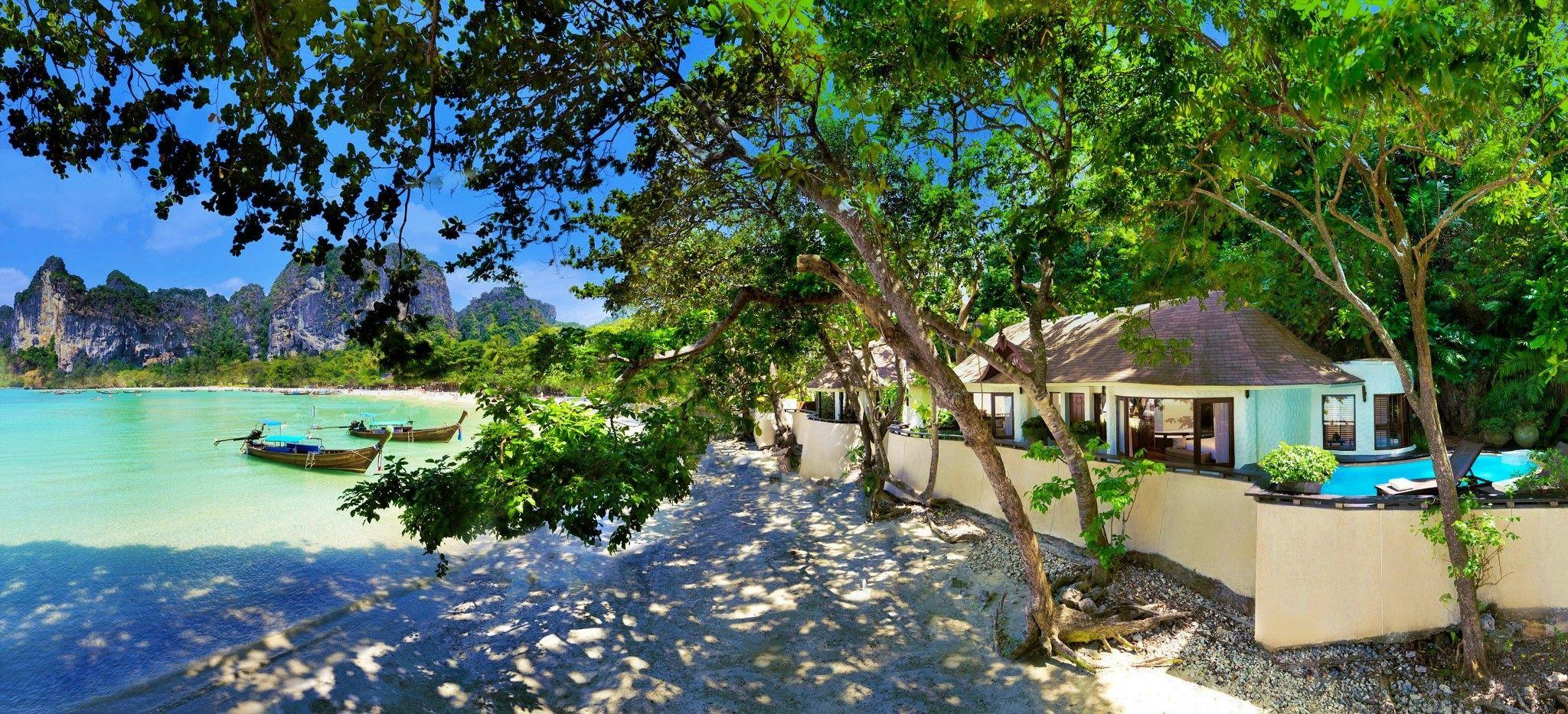 Eine Villa am Strand, der im Schatten großer, wilder Laubbäume liegt