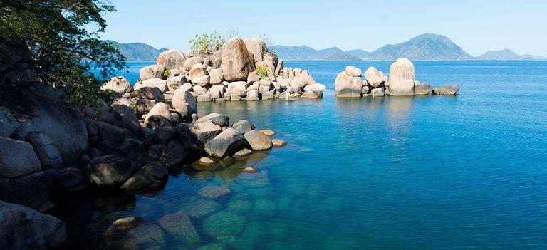 Blick auf den blauen Malawisee, die andere Küste in der Ferne, Felsen im Bild