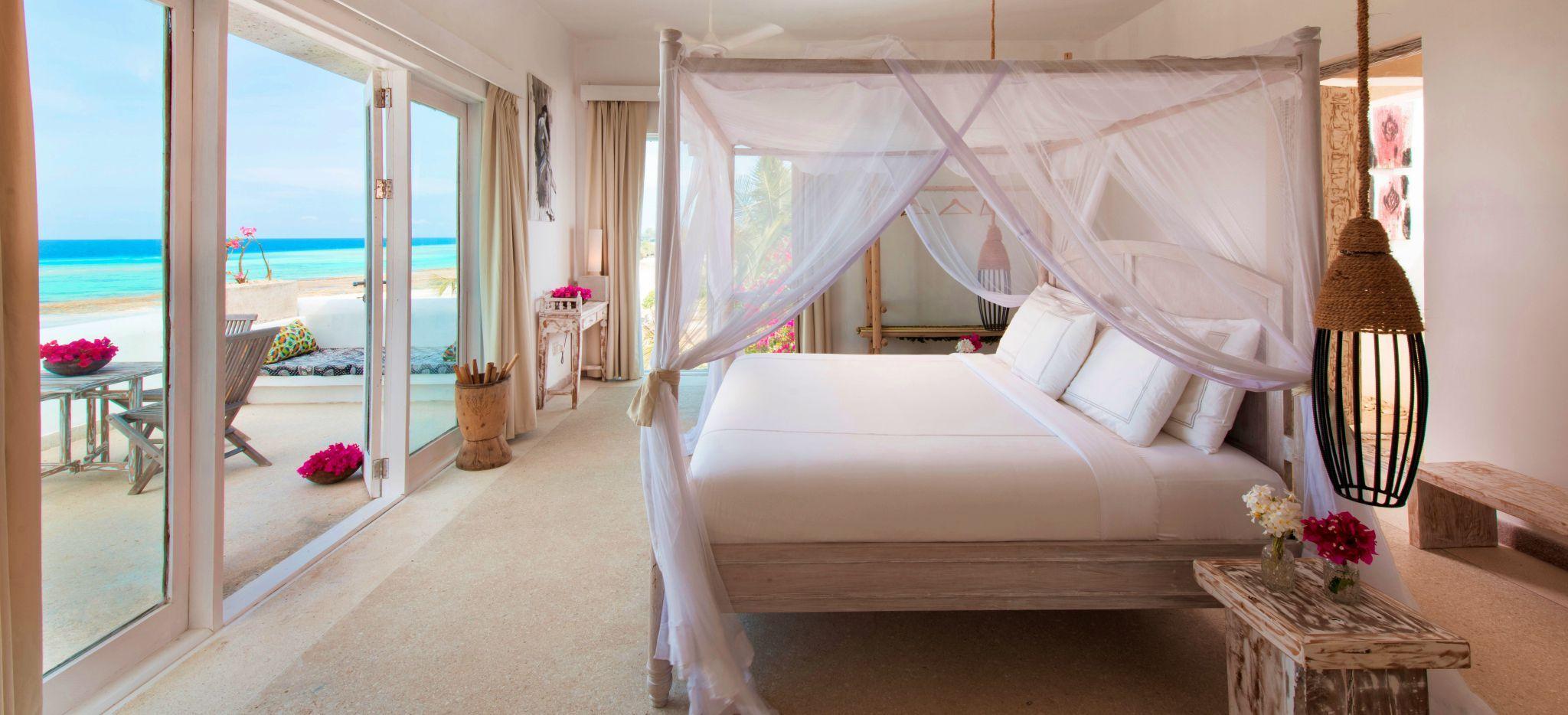 Ein Bett in einem hellen, fast vollständig weißem Schlafzimmer mit Glasfront, durch die man eine Dachterrasse betritt