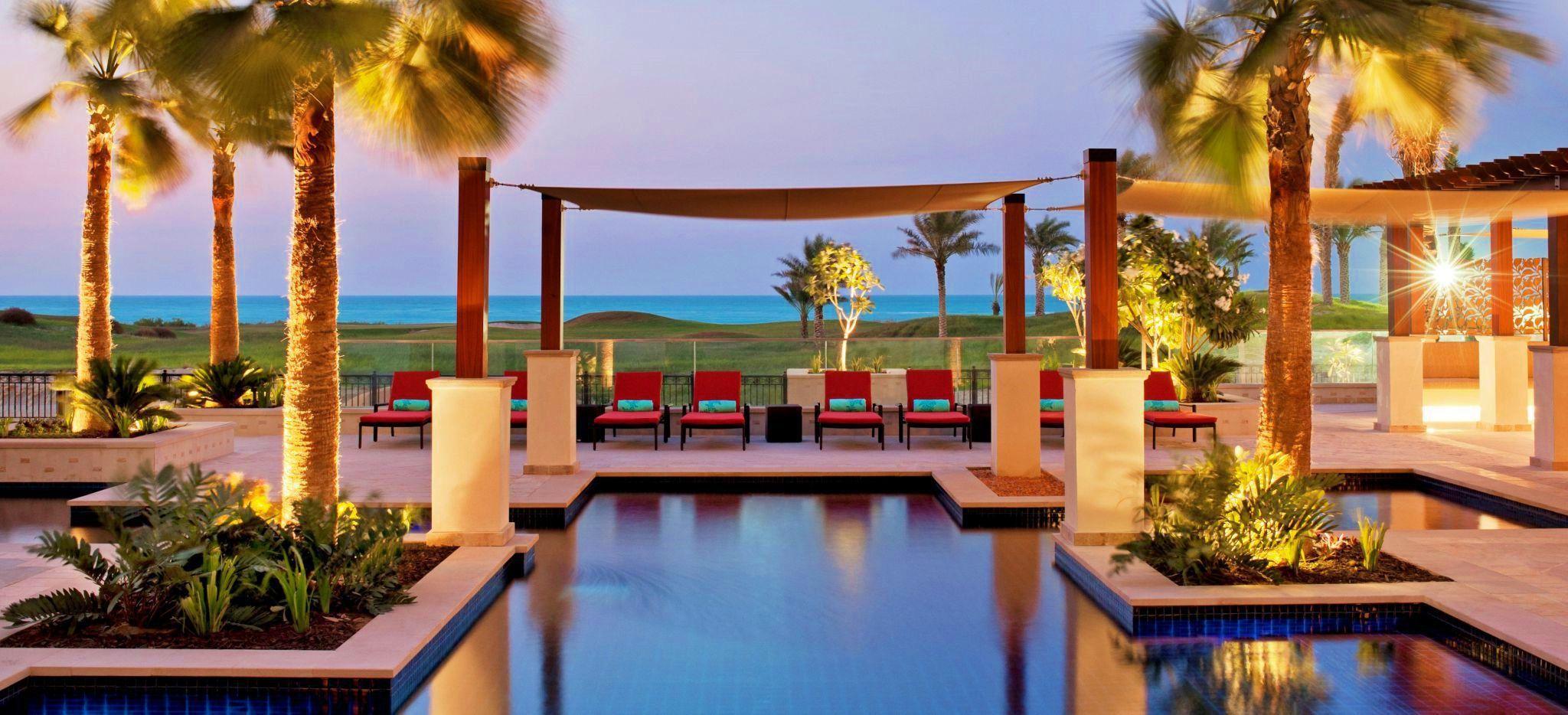 Der Pool des St. Regis Saadiyat Island Hotel. Dahinter eine Lounge sowie der Golfplatz und das Meer. Hell erleuchtet am Abend.