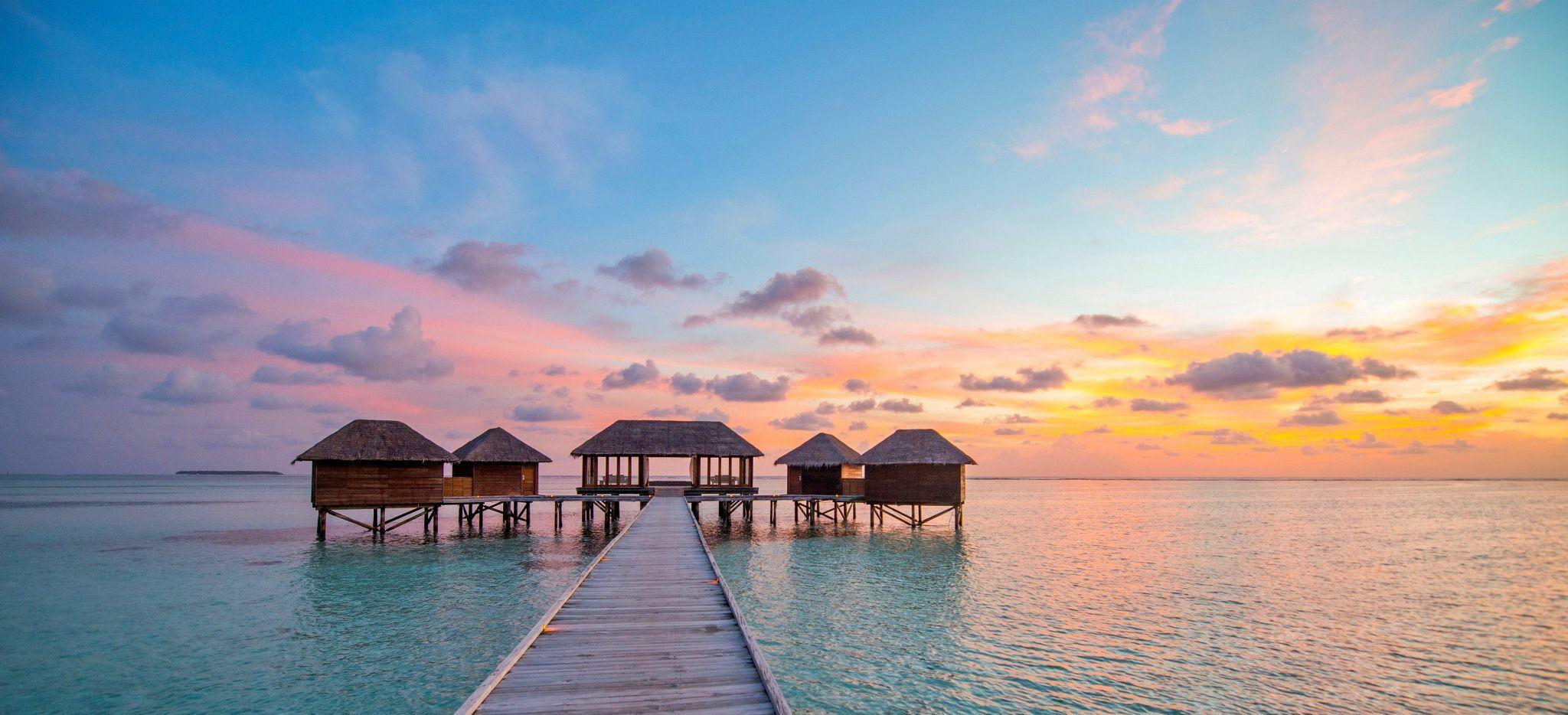 Ein Wellnessbereich in Overwater-Villen im Abendrot im Hotel Conrad Maldives