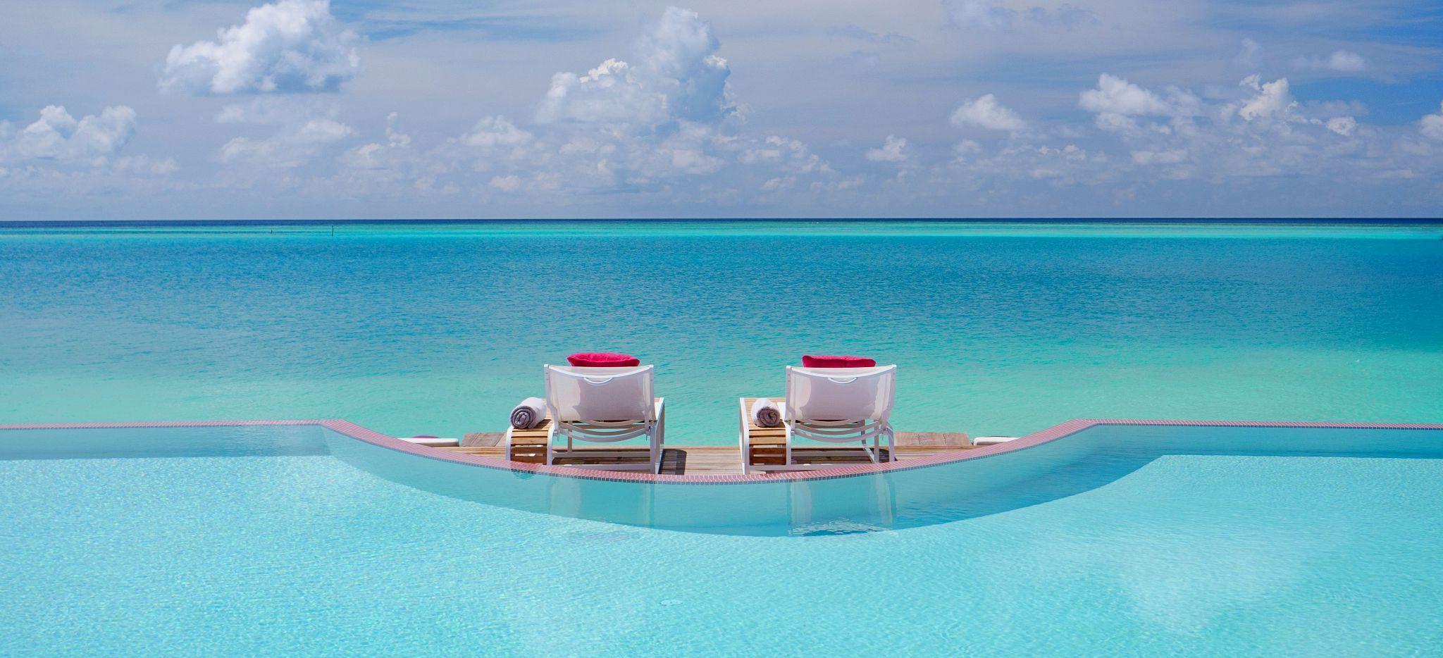 Ein Pool mit Meerblick, davor zwei Strandliegen