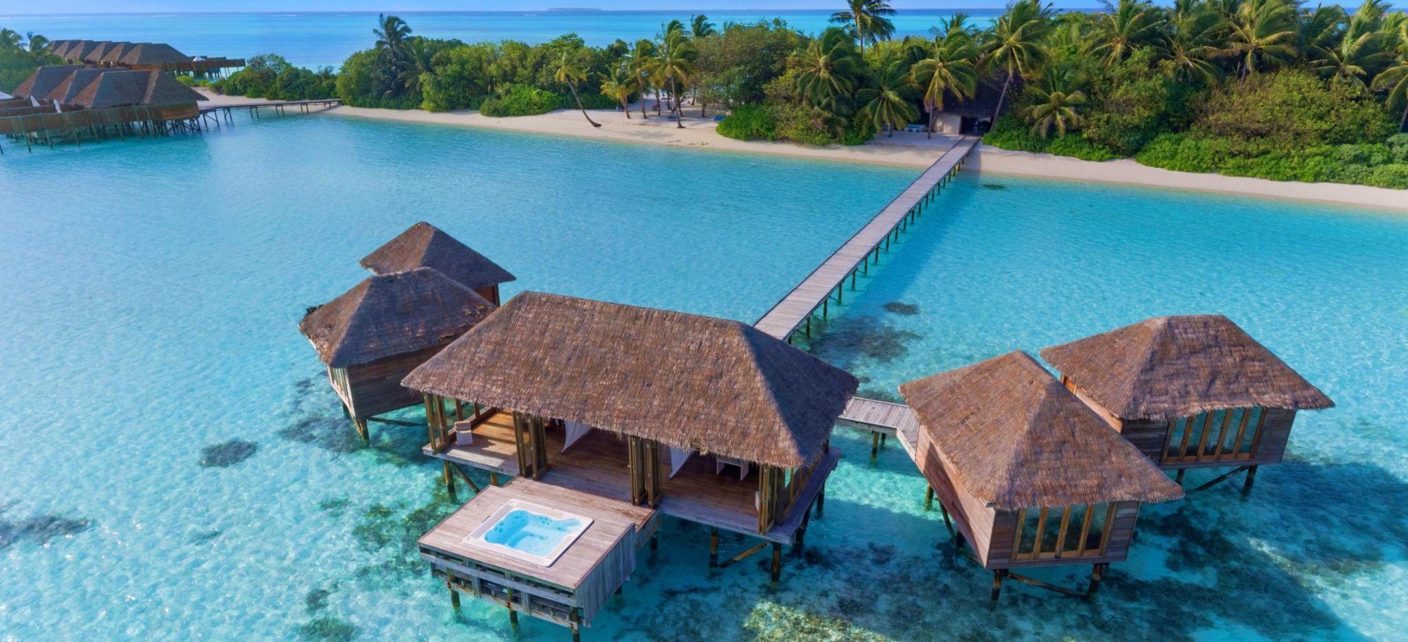 Eine Wasservilla, in der sich ein Wellness-Bereich befindet. Im Hintergrund die Hotelinsel Conrad Maldives