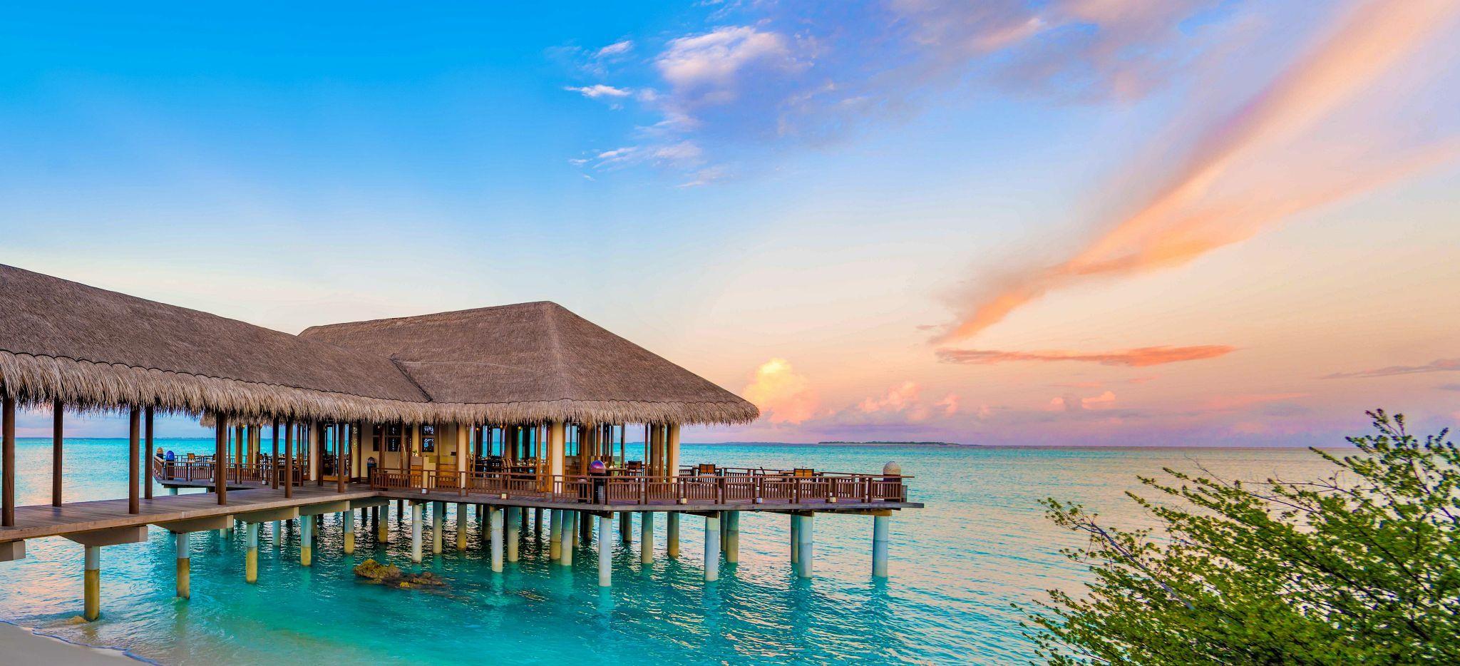 Ein Restaurant auf Stelzen in der Lagunde der Malediveninsel Hideaway Beach