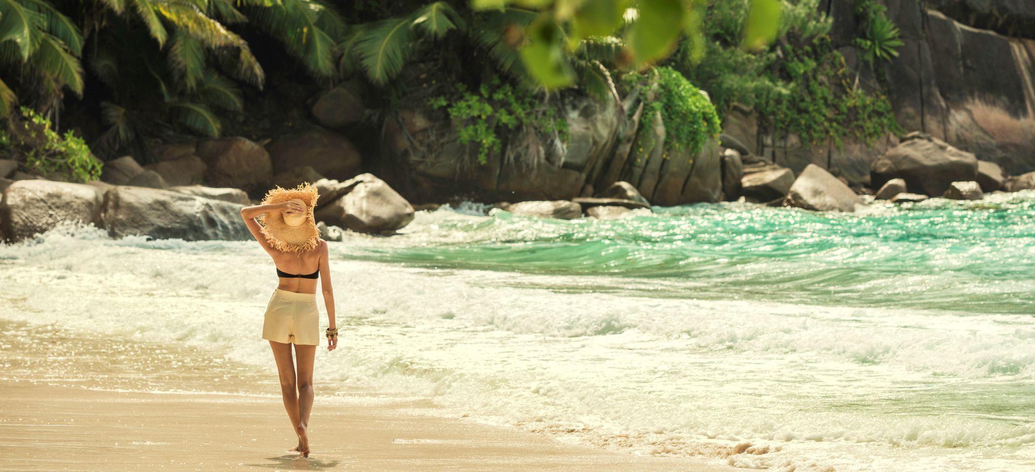 Schöne Frau mit Sonnenhut wandert den Strand Petit Anse vor dem Hotel Four Seasons Resort Seychelles entlang