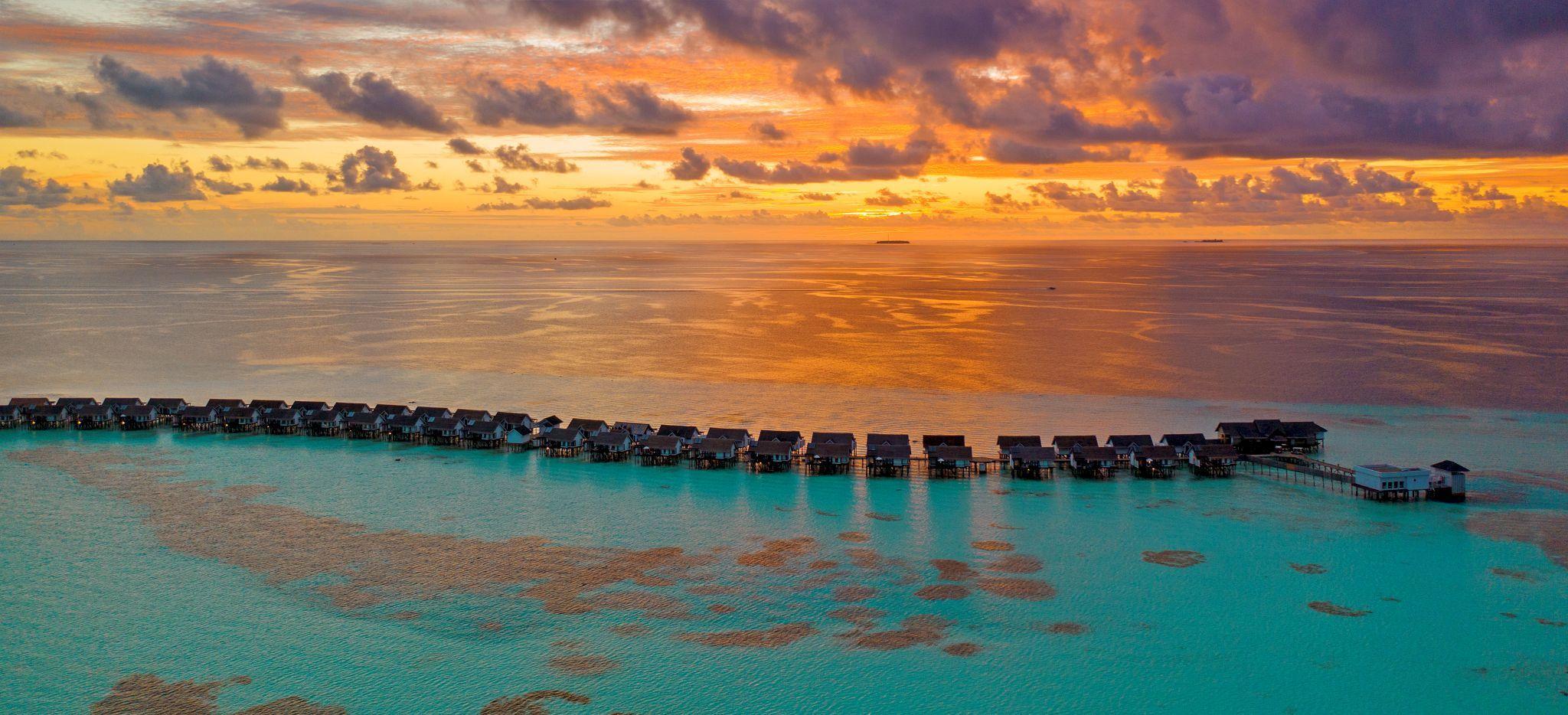 Der Sonnenuntergang über den Wasservillen des Hotels OZEN auf den Malediven