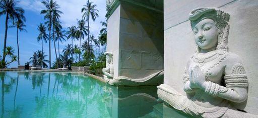 Buddhistische Statue in den Stein um einen Pool geschlagen, im Hintergrund Palmen. Das Hotel Kamalya auf Koh Samui in Thailand