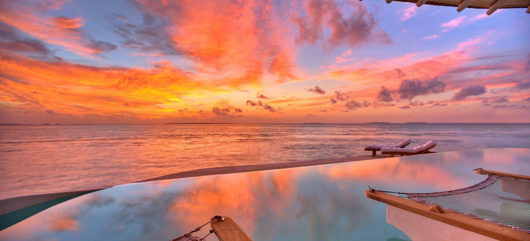 Ein Sonnenuntergang von einem privatem Pool einer Wassevilla auf den Malediven aus gesehen