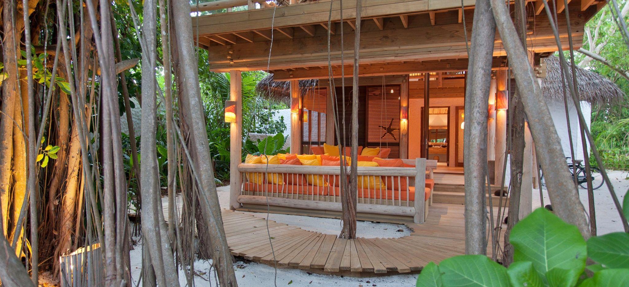 Eine hölzerne Terrasse im Sand umgeben von Lianen, vor einer Villa des Hotels Soneva Fushi, Malediven