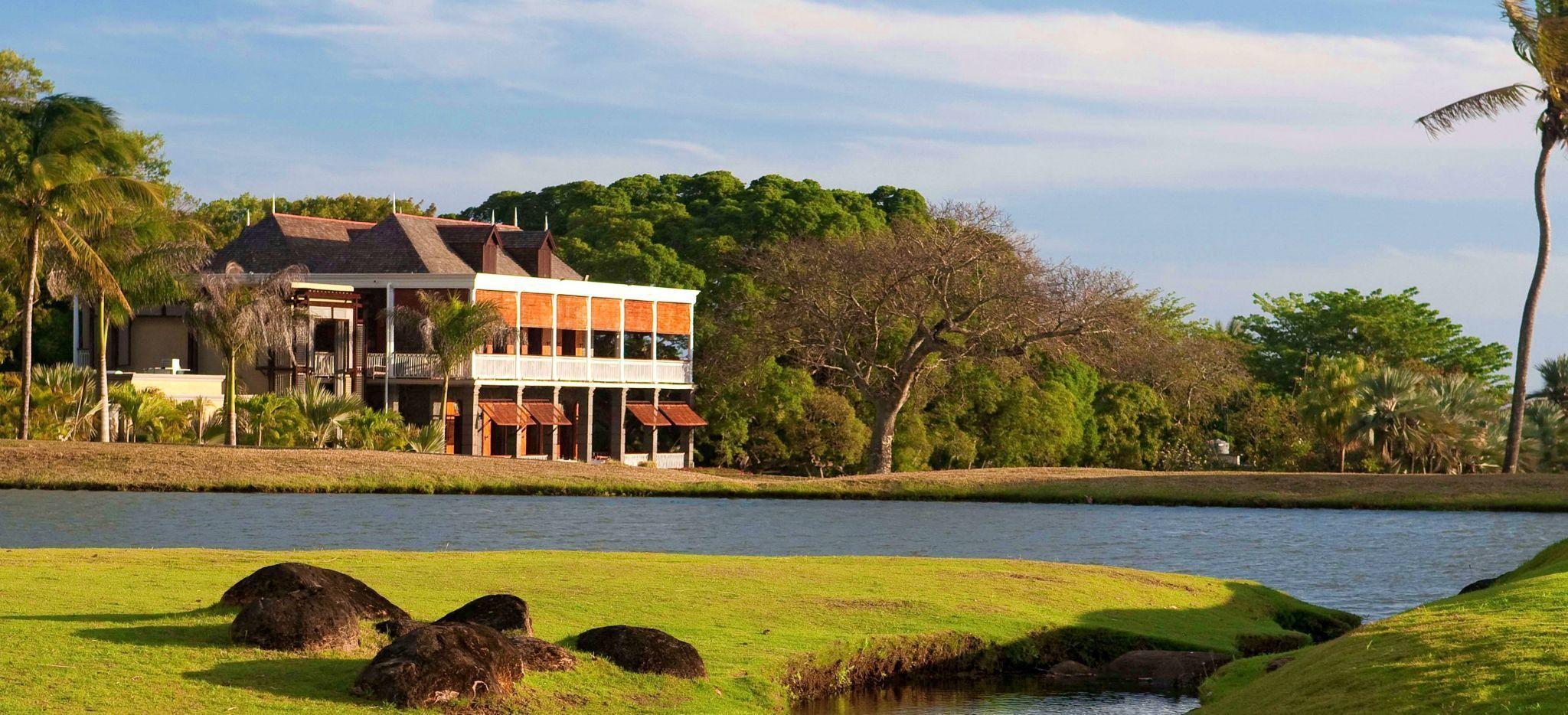 Ein Hotelgäude im tropischen Wald hinter einem kleinen See