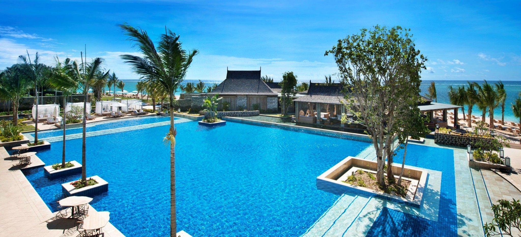 Ein großer Pool mit Strandliegen und Palmen