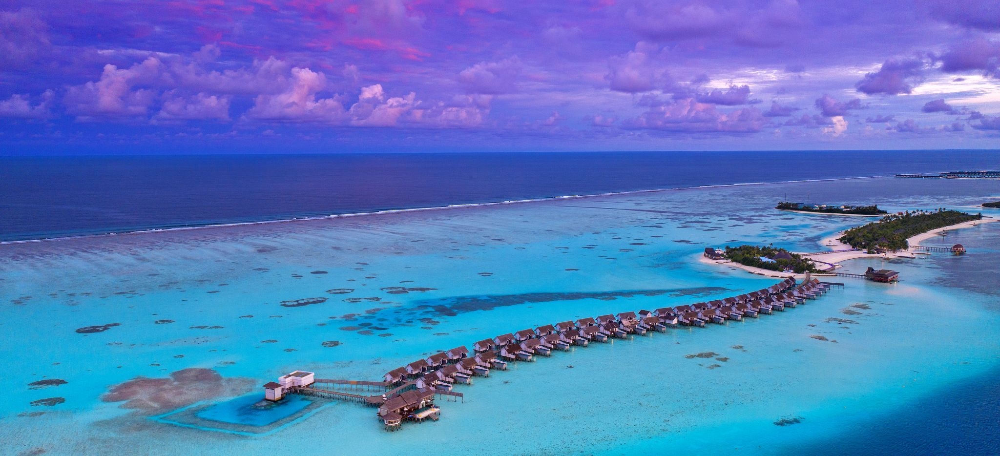 Luftaufnahme einer Malediven-Insel mit Wasservillen, das Hotel Ozen by Atmosphere im Abendlicht.