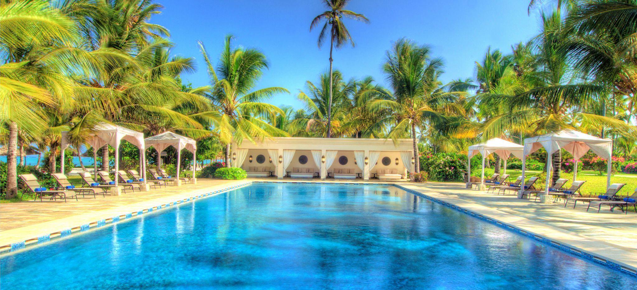Ein Olympischer Pool, umringt von Sonnenschirmen, Strandliegen und einem omanisch-arabischem Haus