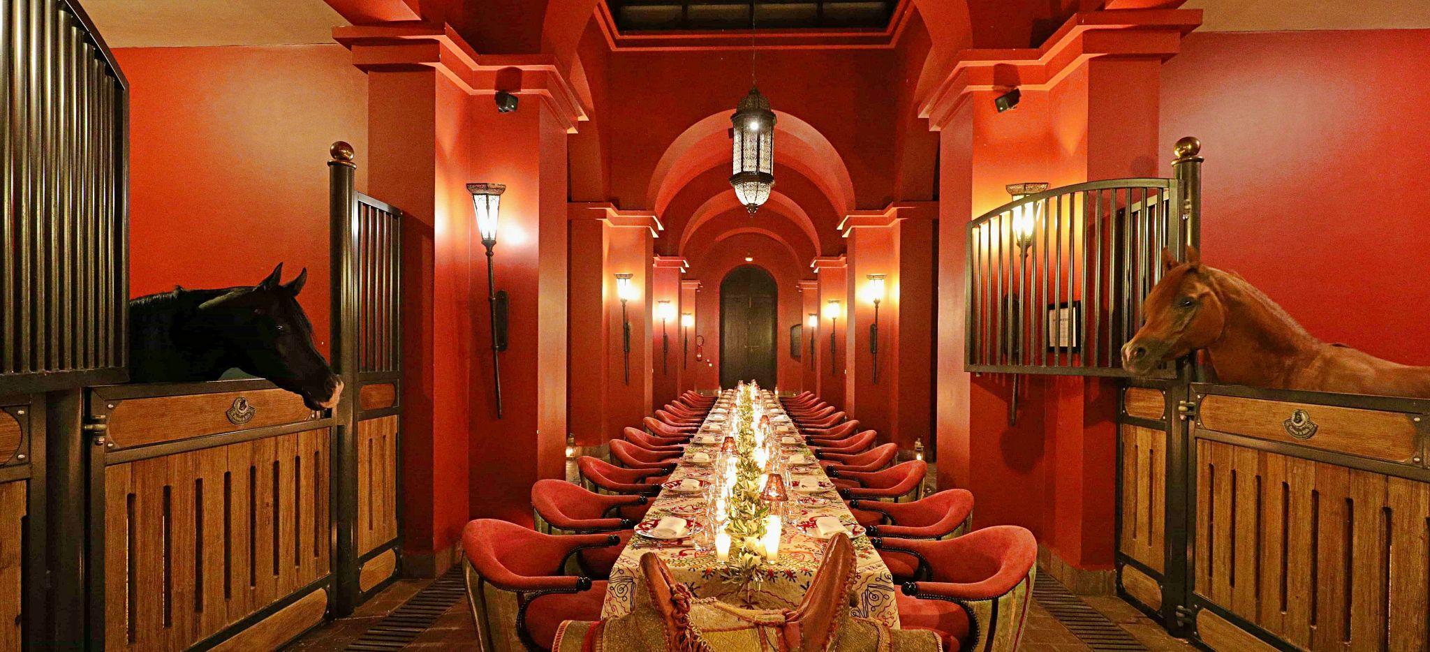 Lange Tafel im Stall des Hotels Selman in Marokko, gedeckt für Dinner